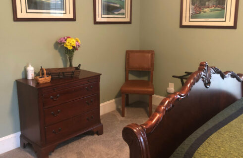 Brass bed made up with cute quilt picturing bears and a cabin next to a wooden nightstand and lamp.