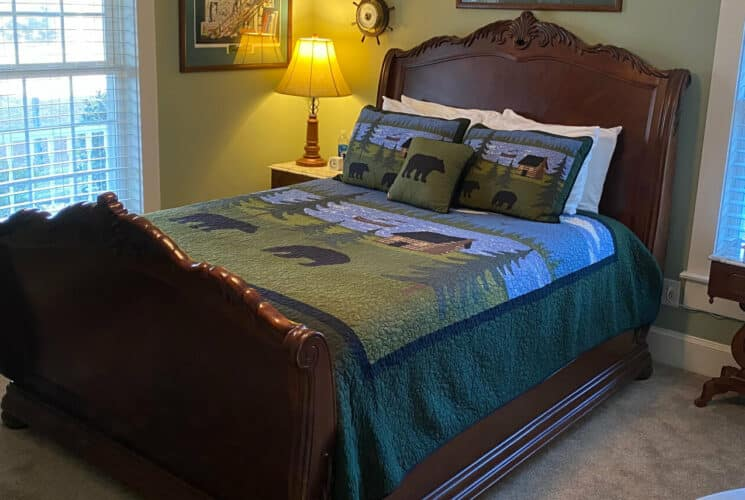 Brass bed made up with cute quilt picturing bears and a cabin next to a wooden nightstand and lamp in a room with large windows.