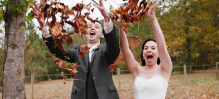 Young and happy bride and groom throw autumn leaves up into the air exuberantly.