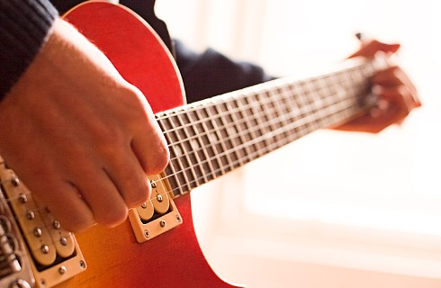A man's hands play a red electric guitar.