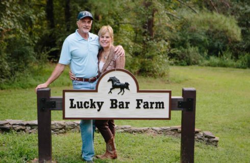 Man in blue and woman in tan stand behind a sign with the words Lucky Bar Farm.