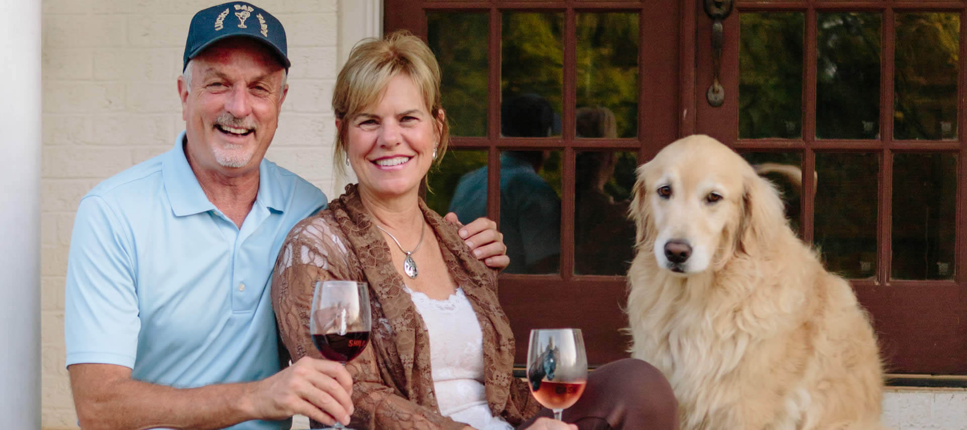 Smiling couple on a porch hold wine glasses next to a golden retreiver.