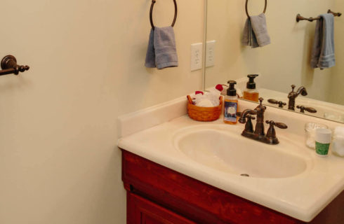 Cherry vanity with a white sinktop and bronze fixtures in a bright bathroom.