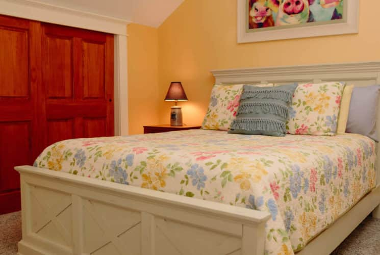 Farmhouse white sleigh bed with a flowered spread and severall pillows in a yellow bedroom.