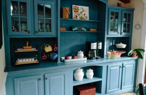 Large blue breakfast buffet set with k-cups, colorful mugs, and a coffee maker, along with cabinets full of glassware.