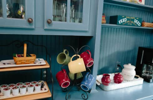 Large blue breakfast buffet set with k-cups, colorful mugs, and a coffee maker.