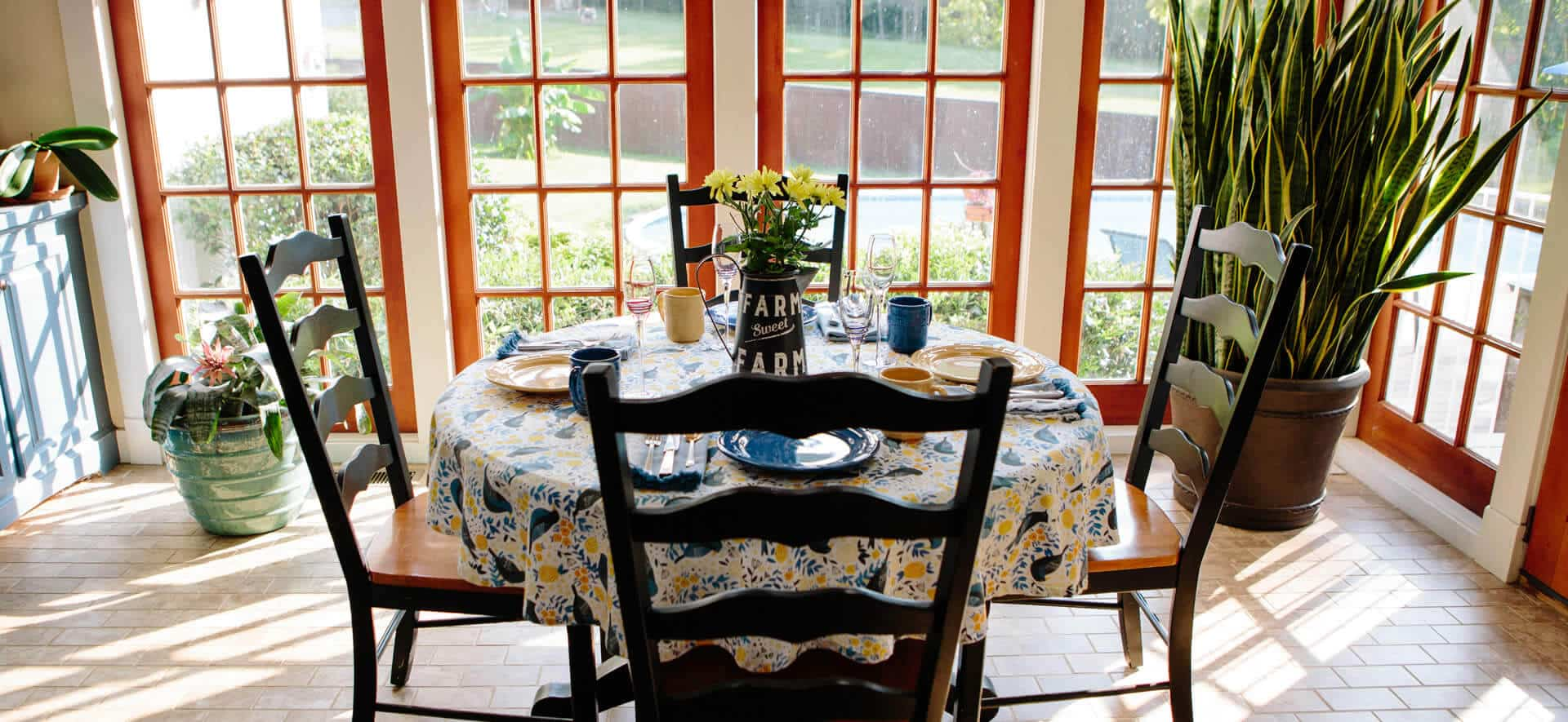 Small four-top table with a flowered cloth in front of a large window in a bright and airy breakfast room