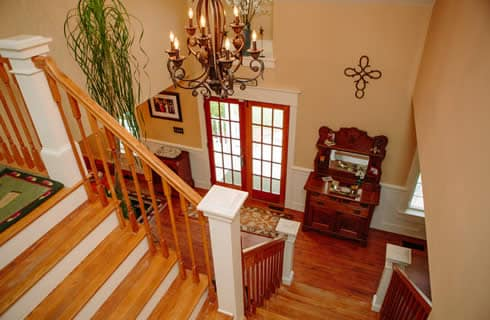 View of foyer from staircase landing - wooden floors, wooden star rails and an antique dresser.