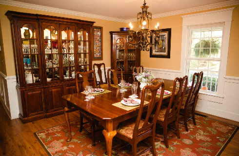 Dining table set for six in a warm and bright dining room with a white buffet and wooden floors.