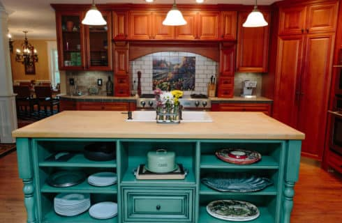 Expansive inn kitchen with cherry wood cabinets and a large island painted teal with a butcherblock top.
