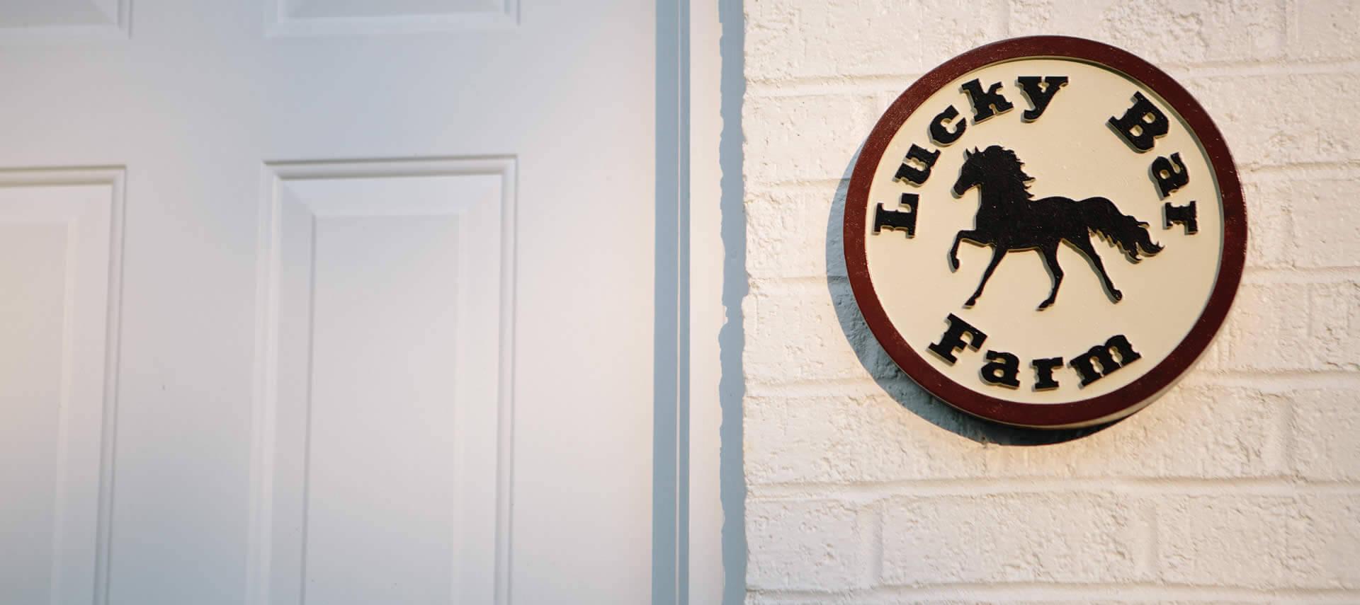 Lucky Bar Farm logo on a plaque ona white brick wall.
