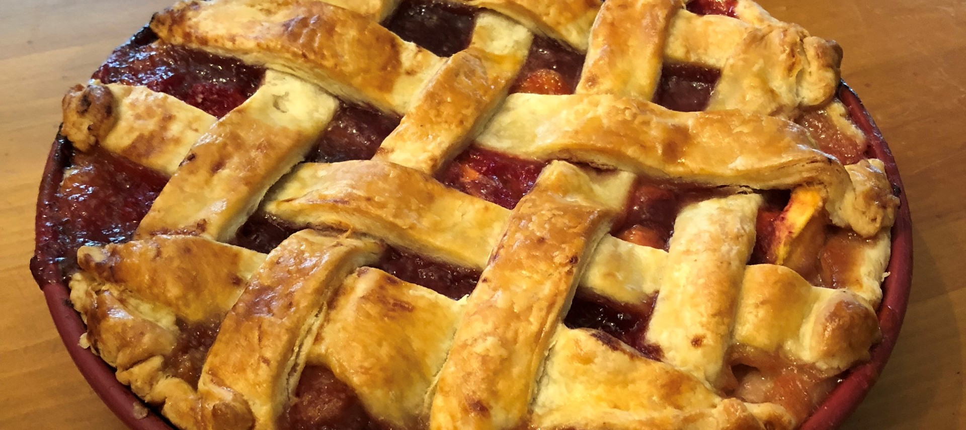 Cherry pie with a lattice crust in a red pie plate on a butcherblock counter.