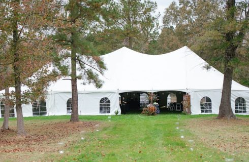 Large event marquee tent with windows set into a grass yard with autumn and pine trees.