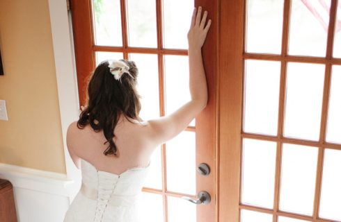 Bride with long dark brown hair and strapless white wedding gown looking out medium woodcolored double french doors.