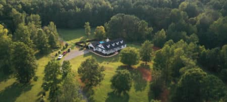 Arial view of large farmhouse with a black roof and dormers, with a swimming pool and manicured lawn.