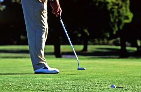 Man's legs; and his hands holding a putter on a golf course with ball falling into hole in foreground.