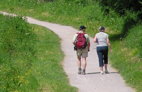 A man and woman walk up a path through a grassy area with a wooded bank on the right hand side.
