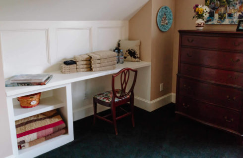Built in desk in white with a small wooden chair next to a cherrywood dresser.