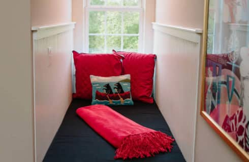 Cute narrrow hidden window seat with a green cover and red pillows and throw.