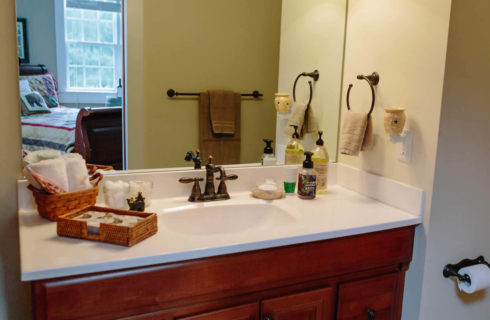 Large cherry vanity with a white sink top with antique bronze fixtures and large mirror.