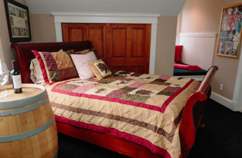 Cherry sleigh bed with a forst animals quilt in tan and red with a Robert Mondavi wine barrel as a nightstand.