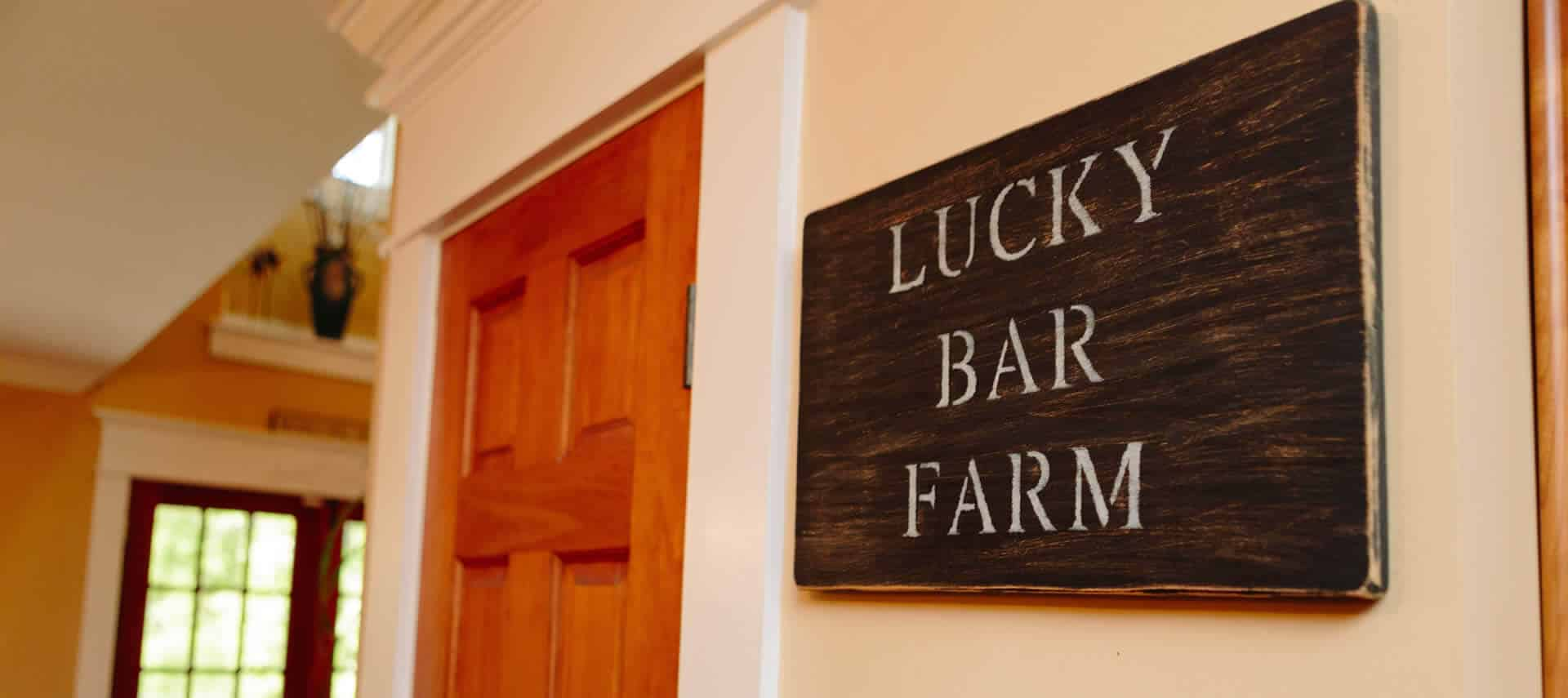 Sign on wall next to a cherrywood door with the words Lucky Bar Farm.
